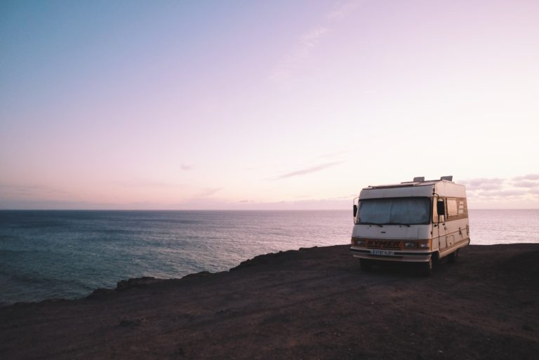 RV parked beside the edge of island during sunset