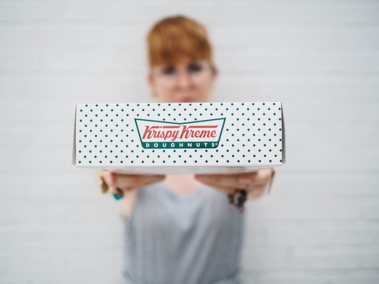 woman showing Krispy Kreme box